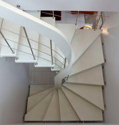 Escalier suspendu 3/4 tournant avec main courante débillardée en bois laqué et marches en béton ciré.
