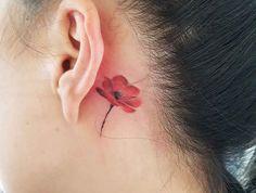 petit tatouage coquelicot derriere l'oreille rouge femme