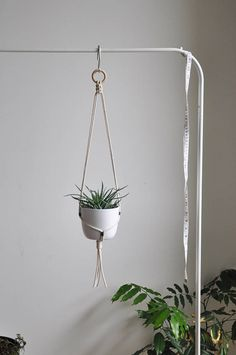 Simple, modern macrame plant hanger with green accents. This pot holder will works great for minimal home decor but also for scandi or boho interiors. READY TO SHIP in 1-3 business days  >> color: cream/beige white with green accents  >> measurements: (pot and plant are NOT included)  white pot diameter 11cm (4,3 in) height 10 cm (4 in)  SIZE GUIDE From the top to the bottom (with tassel) 30 inch /75 cm measured without pot so it will be a little bit shorter depending on...