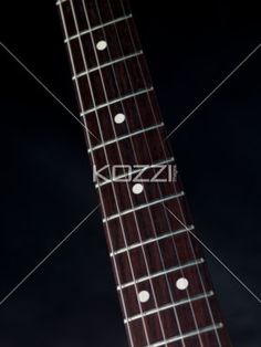 cropped image of a fret board on dark background. - Close-up cropped image of fret board with strings against black background.
