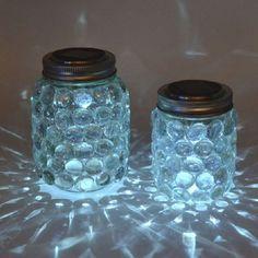 bocaux remplis de gravier en verre et transformés en lanternes