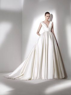 Pronovias' latest range - Calamian. This simple but fashion-forward style is made with mikado silk. The deep V-neck, draped sash and wide skirt will nip you in at the waist.