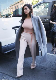 Kim Kardashian covers up in Jonathan Simkhai knitted cropped top, high waist trousers and a warm winter coat by Céline.