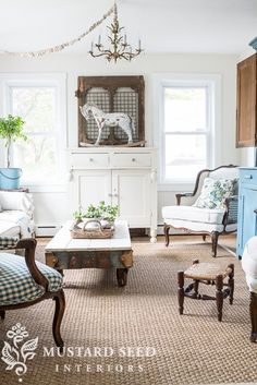 Walls in Pearly White by Sherwin Williams, natural jute rug, whites with wood tones, factory cart table, old screen door as backdrop for rocking horse, chandelier, no window coverings, pretty pillows, fresh greenery