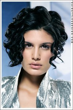 Hair Style: Incredibly sexy and romantic. For a prom, wedding or formal, this fabulous head of hair will definitely turn heads. This woman's hair is parted off the center with the hair styled into springy curls. The curls fall beautifully at the sides and at the face.  Hair Cut: The hair is cut short.  Hair Colour: The hair colour is black.