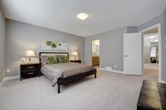 Master bedroom with carpet. Wood frames bed with night stands and artwork.