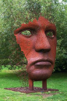 "Rusted steel metal ""Vertical Face I"" sculpture by Rick Kirby. Exhibited amongst trees as part of the permanent collection in Burghley House ""The Gardens of Surprise"" sculpture garden (since 2007), Stamford, Lincolnshire, England, UK."
