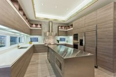This all wood kitchen has wood paneled cabinets and flooring, stainless steel appliances and center island, a marble back splash and ribbon windows around the kitchen. Click through for more images of this Toronto mansion. Tall Kitchen Cabinets, Kitchen Tile, Kitchen Supplies, Kitchen Ideas, Richmond Hill, Traditional Kitchen, Wood Paneling, Future House, Countertops