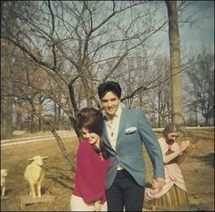 Elvis and Priscilla Presley on the front lawn of Graceland.  They used this picture as their Christmas card picture that year.  The lawn is decorated for Christmas, as it was every year that Elvis was alive and still is by his estate.  Elvis loved Christmas very, very much.
