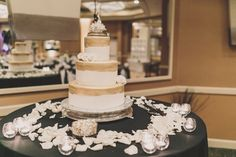 The couple's three-tiered wedding cake was dusted with gold glitter at the top of each layer. Flavors included white cake with raspberry and chocolate mousse and lemon cake with lemon mousse. The cake topper was used by the bride's late grandparents on their wedding day years prior. Photography: Gina & Ryan Photography. Read More: https://www.insideweddings.com/weddings/black-white-gold-wedding-with-glitter-details-in-newport-beach/619/