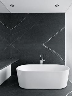 Free standing tub. High contrast. Black stone feature wall