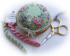"""""""Sunshine and Flowers"""" pin cushion by Lorna Bateman: """"In anticipation of spring - designed to encourage beginners to try a range of simple stitches and show how they can be used to create flowers. I only used perle No:12 in this design - a superb thread to stitch with."""""""