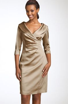 A flattering portrait collar and a wide, low neckline style a dress shaped with princess seams and pleated to give a subtle wrap-like illusion.