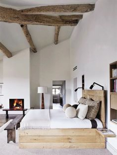 rustic bedroom. modern, clean, white bed linens, wood beams, great pillows and swing arm sconce lights. Fireplace in bedroom, DIY bed.