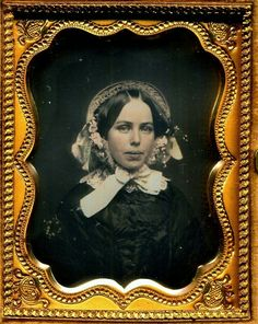 This daguerreotype is simply radiant and wonderful. The coloring is delightful: blue and pink lace, pink flowers, and the subtle tones of her face. Her thick lips give her an exotic quality and her eyes are focused on us. SIZE. Ninth plate. HOUSING. Union case in good condition. Does not close completely. (Continued in comments.)