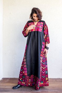 A traditional black Bedouin dress of a young married woman, with bright colored intricate embroidery.  Cotton dress with silk threads, Extraordinary small and very fine cross stiches From The Sinai Desert or the Negev, from about 1920.  Beautifull ethnic piece in a very good condition  SIZE:  US size – M– L 10-12 Europe size – 38-42  Bust – 42 = 108 cm Hips – 52 = 133 cm  Length of the dress from shoulder to floor – 55 = 140 cm   Sleeves width, circumference at upper part 17 = 43 cm Sleeves…