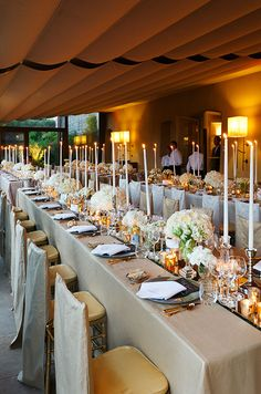 Banquet tables set for 16 guests are draped in fabulous cream-colored linens.