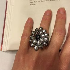 Flower statement ring. Fits Size 7-9 comfortably. Mirrored flower statement ring with silver-tone and tiny black beads. Adjustable stretch  from size 7 to 9. Slight tarnish on bottom of band but you cannot see it at all when wearing. Jewelry Rings