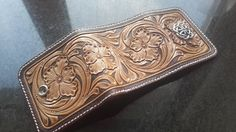 The purse is made of genuine leather of a vegetable tanning. It is decorated with a flower pattern in Sheridan style by method of a cold stamping on