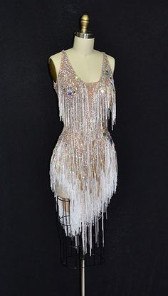 Short, white latin dress with heavy stoning, fringe, and an open back from Designs to Shine by Maria McGill. Visit http://ballroomguide.com/comp/attire/lady.html for more info about competition attire.