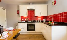 Red tiled kitchen at Lake Road Apartment in Keswick Kitchen Tiles, Kitchen Design, Kitchen Cabinets, Red Tiles, Luxury Apartments, Kitchen Inspiration, Lakes, Catering, Cottage