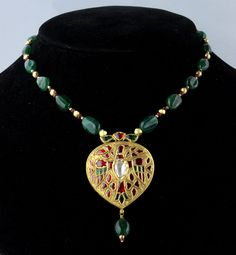 A fine Gold, ruby, emerald and diamond pendant necklace circa 1950  The heart shaped yellow gold pendant finely engraved and inset with cabochon rubies and emeralds in the form of a winged eagle with single flat cut out diamond centre on a cabochon emerald gold bead and ruby bead necklace, the reverse finely enamelled on a red ground.
