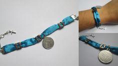 Pulseira em cetim turquesa com aplicações de metal prateado. Com pendente em formato de moeda e fecho de mola prateado. Tamanho: Ajustável entre 16 a 20cm. Peça manufaturada.  Referência: DE010