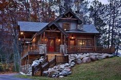 Beautiful log cabin home:  What a cool log house.  Love the stones and bright red door.