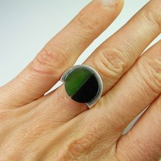 A timeless iconic classic solid sterling silver ring hand made and set with two lovely sections of natural earth mined semi precious stones- and onyx half moon and a nephrite green jade half moon.  The design with the intersecting curves and arcs is eye catching and very pleasing to look at.  This mid century one of a kind ring has an adjustable shank and will fit most ring sizes.  In total it weighs 6.2 grams and is very comfortable to wear.  It is in mint condition  The face of the ring…