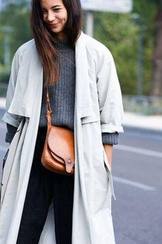 ニットにブラックのパンツを合わせ、上から抜け感のあるグレーのロングアウターを羽織ったスタイル。ブラウンのレザーバッグがナチュラルな雰囲気を出していていいですね。