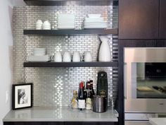For the huge double ovens, HGTV's Kitchen Cousins built a dark wedge cabinet, an elegant contrast to the white lacquer throughout the rest of the kitchen. The cousins outfitted the homeowner's espresso bar area with a shining stainless steel backsplash.