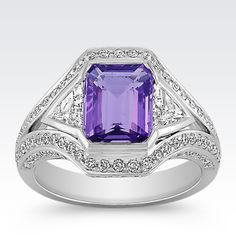 This exquisite design is part of our exclusive One-Of-A-Kind collection. One emerald cut lavender sapphire, at 2.36 carats, and two trillion shaped diamonds, at .58 carat TW, are set in superior quality 14 karat white gold.  One hundred and two round diamonds at  .64 carat TW surround these brilliant gems in sparkle. The total gem weight of this brilliant ring is 3.58 carats.