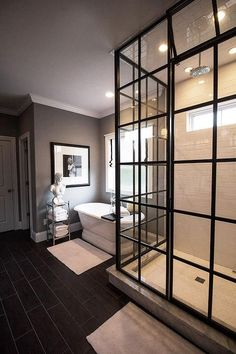 Amazing master bathroom boasts a freestanding oval tub and a Pottery Barn Metal Etagere, placed under window dressed in a black and white roman shade, is situated next to a glass and steel shower enclosure clad in white subway tiles.