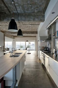 Loft-style kitchen. We love the ceilings and the huge (18x18?) tiles on the floor. Plus the uniquely-shaped countertop. It's just so cool!
