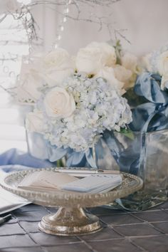The prettiest pale blue hydrangeas + ribbon and creamy white roses + crystal + silver .... very romantic floral combo.