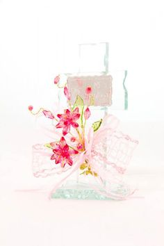 Baptism party favors made out of a glass cross with a pink crystal flower arrangement on top of pink ribbon and a silver plaque with the occasion on it.