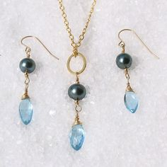 Hana Maui Online Jewelry : With simple elegance, Tahitian black pearls are exotic yet classic, sensuous while remaining refined. In ancient times pearls were appreciated to a level approaching worship.  This Pearl is paired with a beautiful blue topaz in a marquise cut. The soft blue of the gem reflects throughout the pearl.  Light plays off the delicate link of the chain adding movement and depth. These thoughtful touches add a subtle refinement and a balance of blues to complement the…