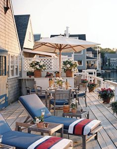 On the deck of this waterfront home designed by Gary Mcbournie, Crate & Barrel deck chairs and umbrellas keep to a blue-and-white theme, with splashes of red from Ralph Lauren Home beach towels.