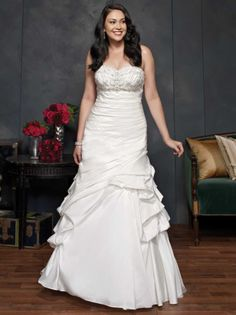 Searching for Plus size wedding dresses with a gathered skirt and pick ups? Here is a strapless wedding gown that has a beaded bust line and ruched bodice. Get more plus size wedding dress inspiration at https://www.dariuscordell.com/featured/plus-size-wedding-dresses-bridal-gowns/