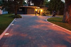 This driveway features Holland, a paver that does exceptionally well in both residential and commercial applications. In this case, antique brown pavers are accented by charcoal edging and paver lights.