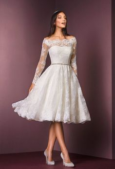 11469: This T-length dress is designed for the modern bride who loves all things vintage. Crafted from corded lace, this is a gown that feels both beautiful and fun. Updated with a contemporary off the shoulder fit and beaded belt, this is a contemporary twist on timeless glamour