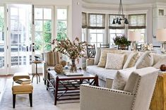 """A """"less is more"""" family room is rich with details, like the nailhead trim on the chairs and geometric coffee table - Traditional Home® / Photo: Michael Garland / Design: Mark Williams"""