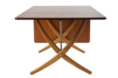 It's a cross-leg dining table with drop leaves in teak with stretchers of brass. Designed by Hans Wegner