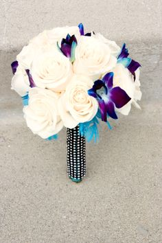the bridesmaid bouquets that were made from with roses accented with blue stem dyed orchids and finished with teal feathers and a jeweled handle