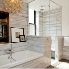 A modern home bathroom in New York City by Plattdana Architects | striped marble tile & picture ledge for artwork over tub