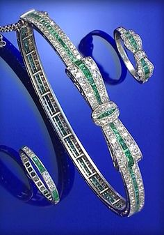 EMERALD AND DIAMOND BANGLE, CARTIER, PARIS, CIRCA 1910, DESIGNED AT THE FRONT AS A BOW...