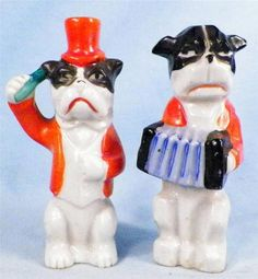 Other dog is playing an accordian. Made in Occupied Japan. Dog with top hat has a microphone. Good vintage condition. No chips, flakes, or cracks. Painted black white, green blue. 3 5/8 tall.