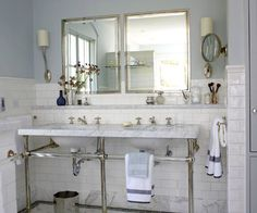 Double Sink Console  This classic double-sink vanity constructed from a single piece of marble set atop chrome legs is just the beginning to the old-world sensibility infused in this charming vintage-style bathroom. Marble baseboards and a bump-out wall shelf unite the vanity to its surroundings, while white subway tile and polished-nickel hardware repeat the vintage flair. Six-inch-deep medicine cabinets tucked behind twin mirrors solve storage necessities.