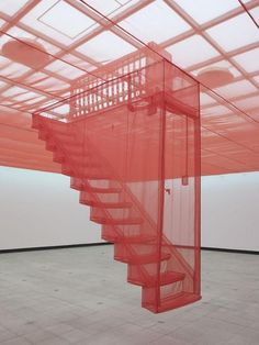 """Door"" by Do-Ho Suh --- ""In an otherwise empty room, Do-Ho had stretched sheer red nylon to create a false ceiling. Suspended from the centre was a fullsize set of fabric stairs, with a door at the bottom, looking like an entrance into an invisible attic. Up close, there were all sorts of neat details, like electrical fittings and a lamp shade."""