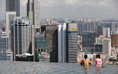 Oaspeţi ai hotelului Marina Bay Sands din Singapore privesc districtul financiar dintr-o piscină aflată pe acoperişul clădirii, luni, 13 mai 2013. (Roslan Rahman / AFP)